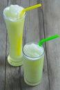 Green Apple juice in glass on wooden table floor.