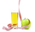 Green apple with juice and tape measure on a white background Royalty Free Stock Photography