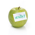Green apple and label with the word healthy isolated on white Stock Photography