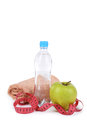 Green apple with measuring tape and bottle of water isolated on white Royalty Free Stock Photos