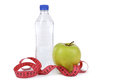 Green apple with measuring tape and bottle of water isolated on white Royalty Free Stock Image