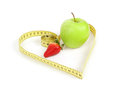 Green apple with a measuring tape and heart symbol isolated strawberry on white background Stock Images