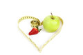 Green apple with a measuring tape and heart symbol isolated strawberry on white background Royalty Free Stock Photos