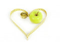Green apple with a measuring tape and heart symbol isolated on white background Royalty Free Stock Image