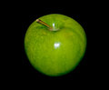 Green apple one shiny isolated in black background Royalty Free Stock Images
