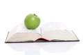 Green apple over a open book Royalty Free Stock Photo