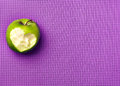 Green apple on a pink yoga mat. Fitness with pleasure. Love to a Royalty Free Stock Photo