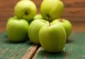 Green apple placed in the fron before other fruit Royalty Free Stock Photo