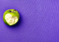 Green apple on a purple yoga mat. Fitness with pleasure. Love to Royalty Free Stock Photo