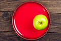 Green apple on a red plate Royalty Free Stock Photo
