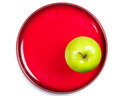 Green apple on a red plate Stock Images