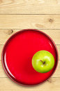 Green apple on a red plate Royalty Free Stock Photography