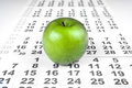 Green apple on sheets of wall calendar closeup Stock Images