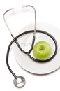 Green apple and a stethoscope isolated on plate Royalty Free Stock Photo