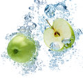 Green apple in water under with a trail of transparent bubbles Stock Photos