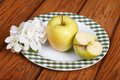 Green apple on a white plate and flowers brown wooden table Royalty Free Stock Photo