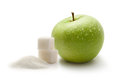 Green apple with white sugar cubes Royalty Free Stock Photo
