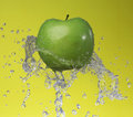 Green apple on yellow background Stock Photos