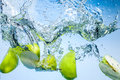 Green apples fruits fall deeply under water with splash a big Stock Photo