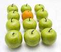 Green apples with one orange Royalty Free Stock Photo