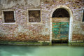 Green arched doorway on a canal in venice italy Stock Photos
