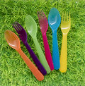 Green background with coloured forks and spoons for a picnic on Royalty Free Stock Photo