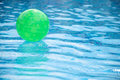 Green ball floating in swimming pool Royalty Free Stock Photo