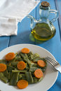 Green beans and carrots salad of in white dish on a blue table next to an oil Royalty Free Stock Image