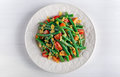 Green beans salad with bruschettas, Red, Yellow Tomatoes and flaked almond on white plate Royalty Free Stock Photo