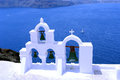 Green bells on santorini island and blue sea with yacht Stock Image