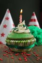Green birthday cupcake with hats in background Stock Photo