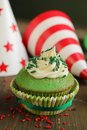 Green birthday cupcake with hats in background Stock Image