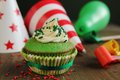 Green birthday cupcake with hats and blower in background Royalty Free Stock Photography