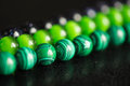 Green and black beads from a stone on background Royalty Free Stock Photos