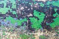 Green and black chipped paint on cement