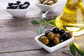 Green and black olives in bowl on a grey wooden background Royalty Free Stock Photo