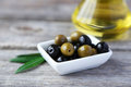 Green and black olives in bowl on the grey wooden background Royalty Free Stock Photo