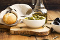Green and black olives in olive oil on wooden rustic board .Ital Royalty Free Stock Photo