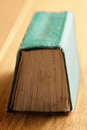 Green book spine up closeup over wooden surface photo Stock Photography