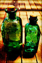 Green bottles still life of apothecary against a wooden table Stock Photo