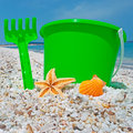 Green bucket and shell starfish by the shore in sardinia Stock Photo