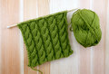 Green cable stitch knitting with a ball of yarn rich coiled rope wool on woodgrain Royalty Free Stock Image