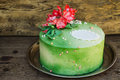 Green cake with sugar flowers on a wooden background Royalty Free Stock Images