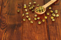 Green capers in spoon on dark wooden table Royalty Free Stock Photos