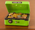 Green cash box with gold and silver coins Royalty Free Stock Photo