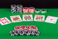 Green casino table with royal flush, red and black chips Royalty Free Stock Photo