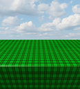 Green checkered tablecloth table with a blank empty picnic cloth in perspective with a plaid pattern on a blue sunny summer sky as Royalty Free Stock Photo