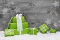 Zelený vianočné darčeky so snehom na šedá drevený