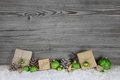 Green Christmas presents wrapped in natural paper on old wooden