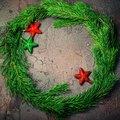 Green Christmas wreath with stars decorations on dark background. Royalty Free Stock Photo